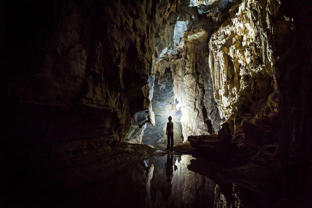 Foto de pessoa em pé numa caverna no Vietnã
