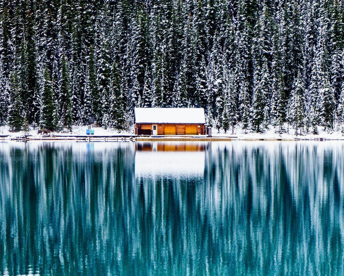 Foto de uma cabana próxima a um lago na neve