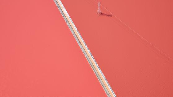 Imagem de uma linha de energia esticada em salina rosada na Califórnia