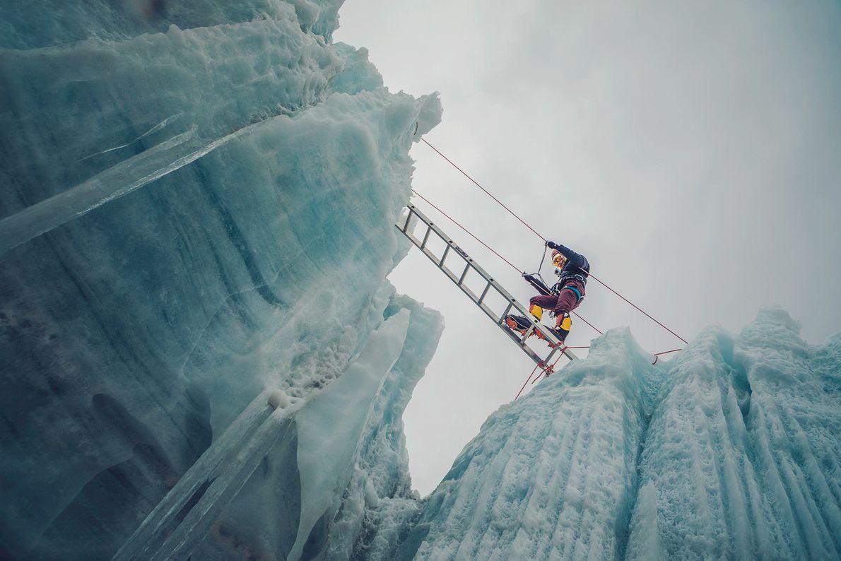 Foto de uma mulher atravessando uma crevasse de gelo nos Himalaias