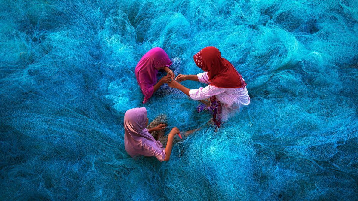 Imagem de uma mãe e crianças que consertam redes de pesca azuis