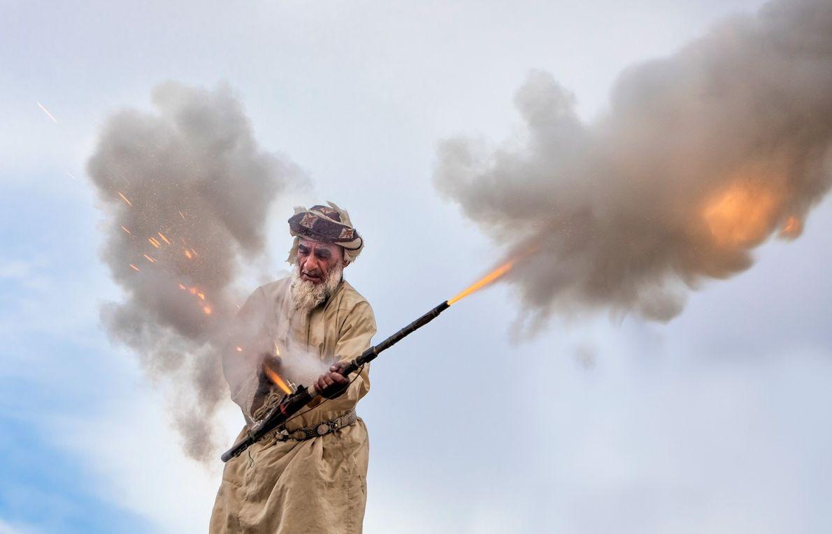 Imagem de um homem disparando um canhão de mão em um casamento de Omã