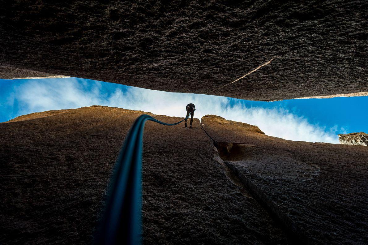 Imagem de um montanhista descendo uma parede de pedra no Parque Nacional Joshua Tree