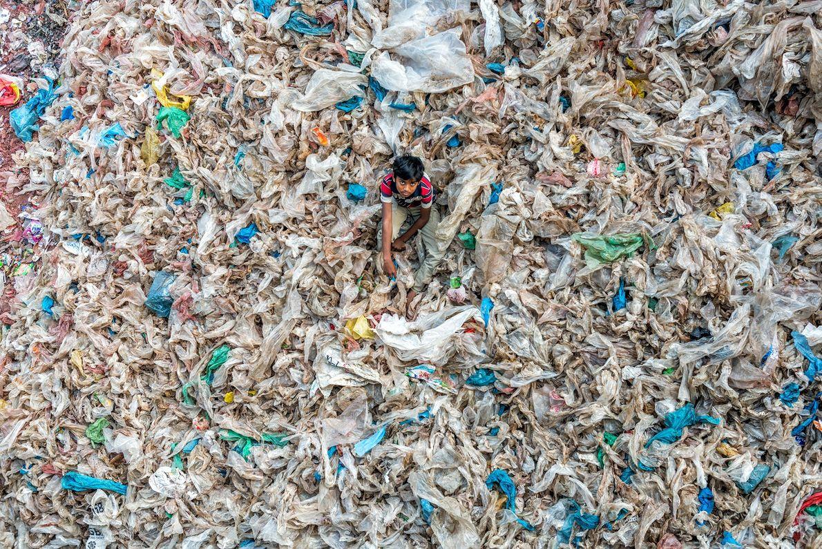 Imagem de uma criança sobre um aterro cheio de sacos de plástico descartados
