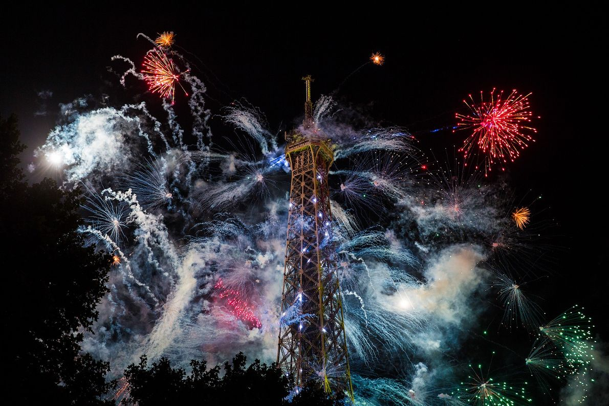 foto de fogos de artifício explodindo atrás da torre eiffel