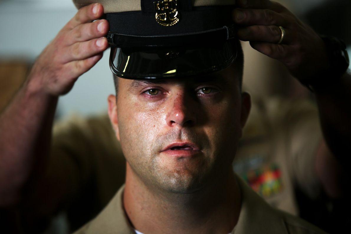 Imagem de mãos colocando um chapéu militar na cabeça de um homem na Marinha dos EUA