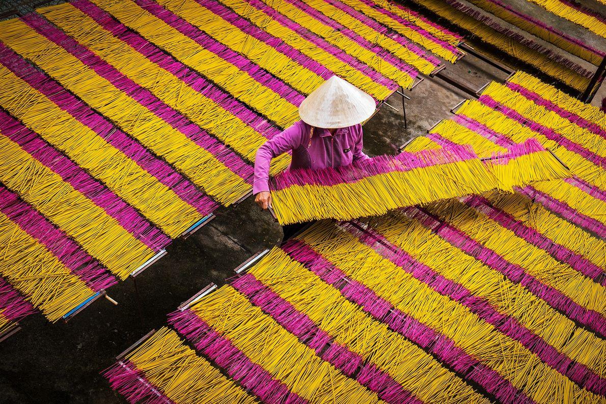 Imagem de uma mulher que trabalha com palitos de incenso amarelo e rosa