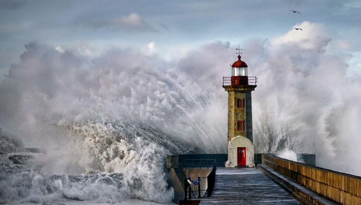 Imagem de uma onda que quebra em um farol em Portugal