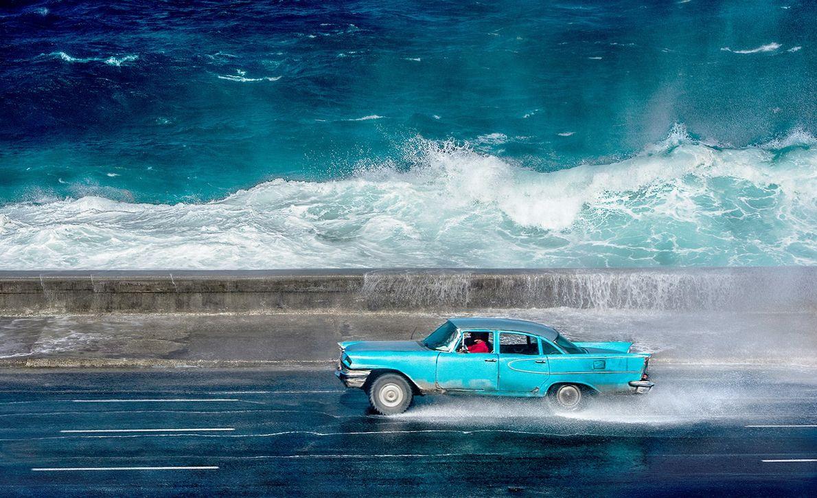 Foto de um carro azul que anda perto do mar em Havana, Cuba