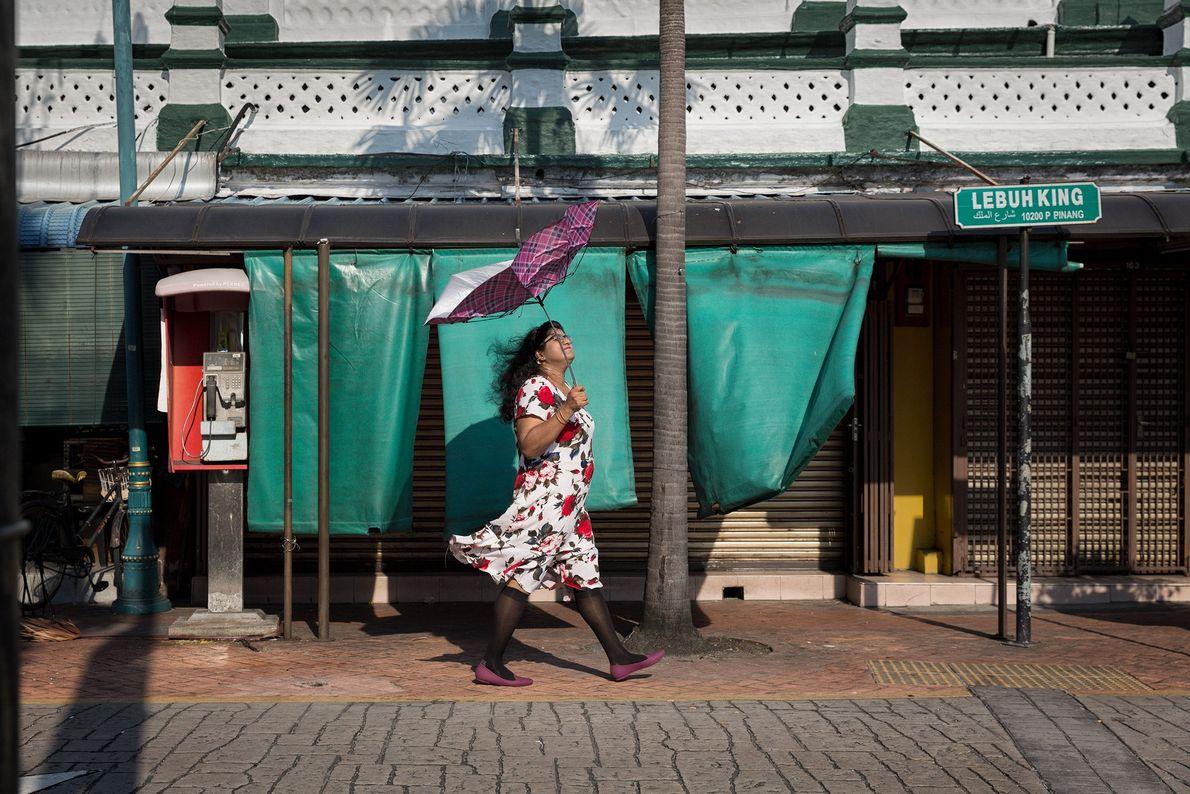Imagem de uma mulher caminhando ao longo de uma rua enquanto carregava um guarda-chuva quebrado