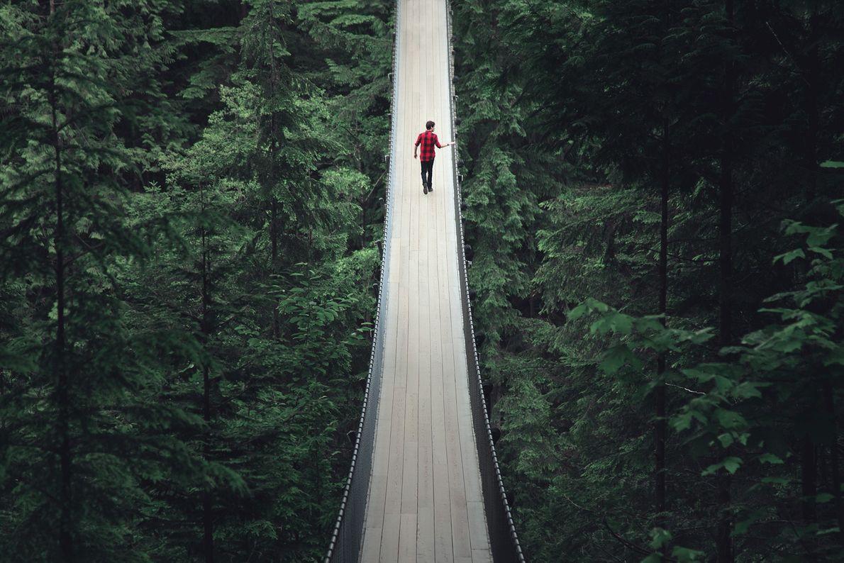 Foto de um homem caminhando sobre ponte suspensa