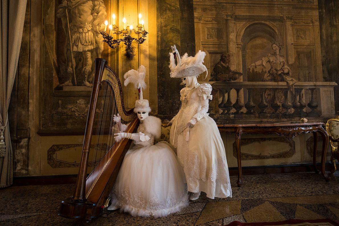 Imagem de duas pessoas em trajes tradicionais de carnaval e máscaras posando com uma harpa