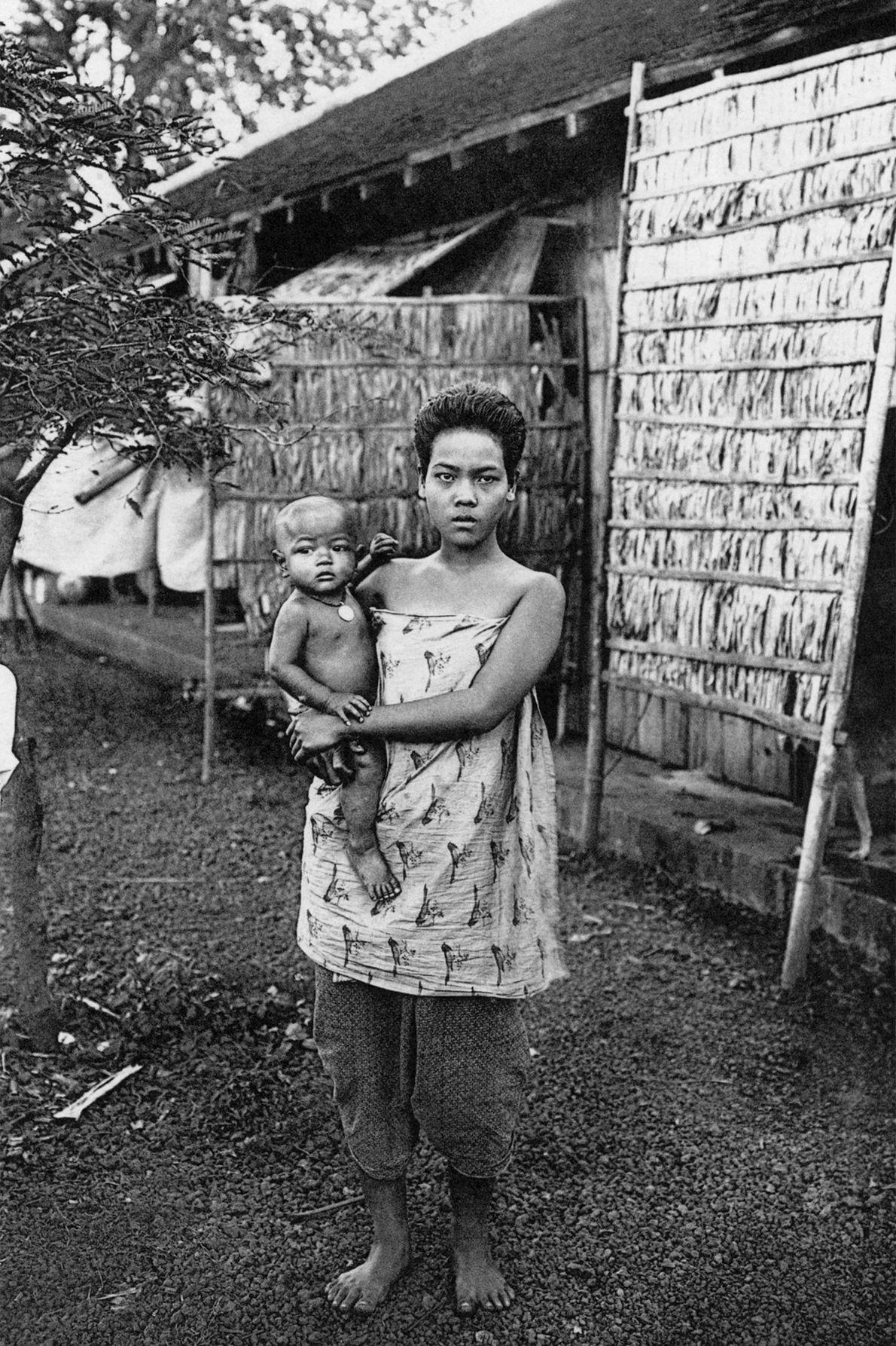 Uma mãe no Camboja equilibra seu filho no quadril.