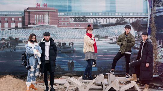 Alunos aguardam para fazer uma prova de artes em frente a cartazes que promovem Fushun, na ...