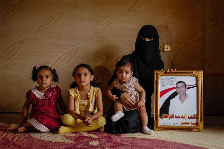 Viúva e suas filhas posam com o retrato do marido e pai, que morreu durante um ...