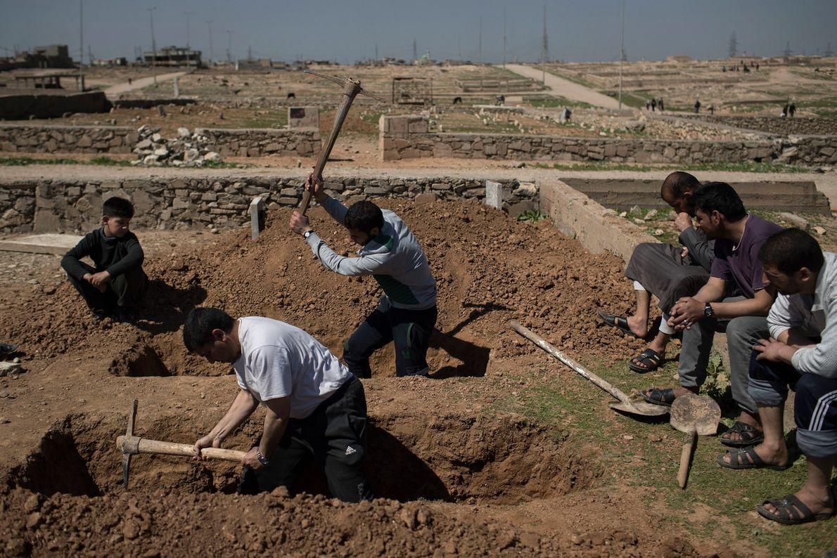Parentes e amigos cavam túmulos para dois civis mortos durante batalha entre forças iraquianas e militantes ...