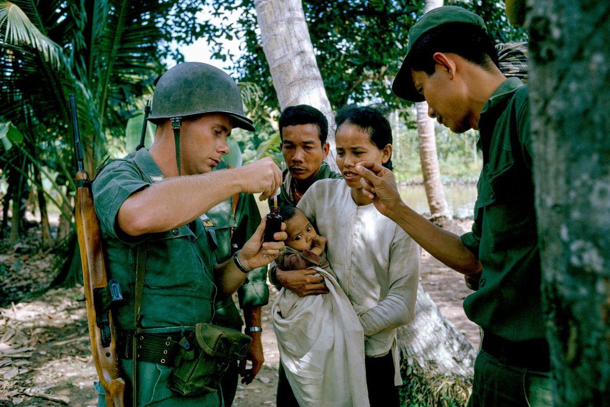 Soldado da infantaria dos EUA demonstra a uma mulher como utilizar um medicamento em gotas em ...