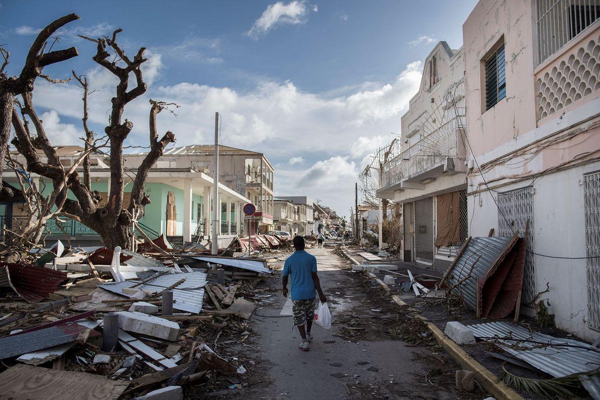 Um homem caminha em uma rua coberta de entulho depois que o furacão Irma atingiu a ...