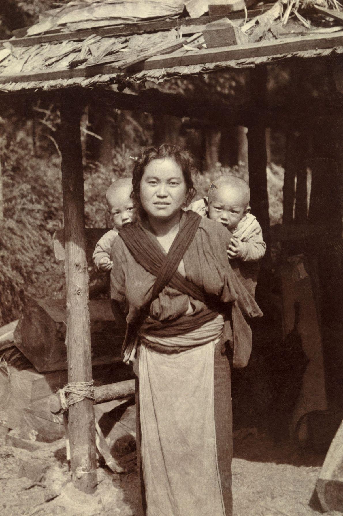 Uma mulher japonesa carrega seus gêmeos nas costas com um pano cruzado.