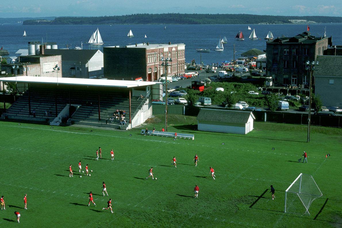 Jogadores participam de um jogo de futebol enquanto barcos a vela passam nas águas próximas durante ...