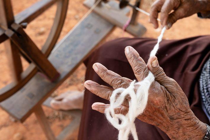 A mão de Dona Maria de Jesus, 87 anos, segura um chumaço de algodão pronto para ...