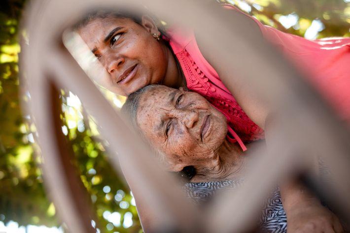 Dona Maria é abraçada por Simone Amorim de Souza, uma das artesãs mais jovens da Associação ...