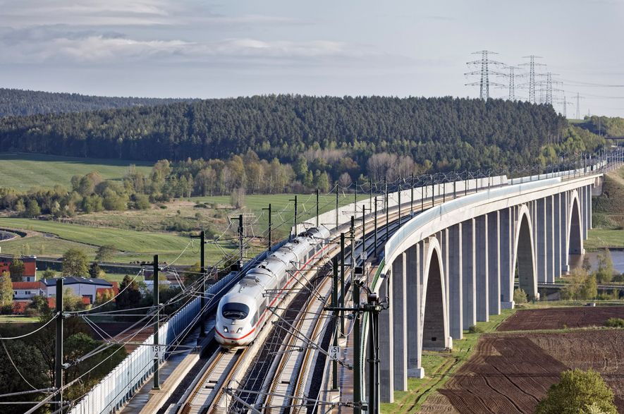 O trem interurbano da Deutsche Bahn passa a altas velocidades pela área rural.