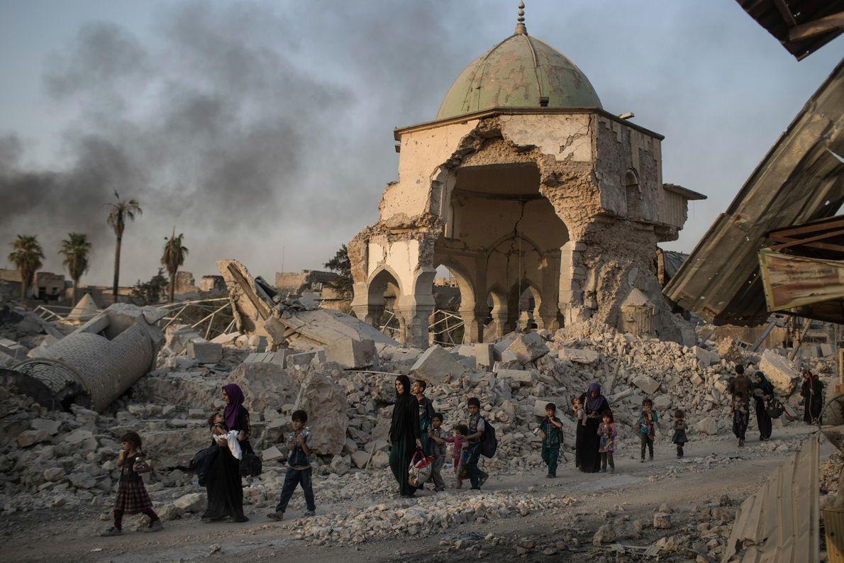 Civis iraquianos refugiados caminham em frente ao mosteiro al-Nuri, destruído durante as batalhas entre forças iraquianas ...