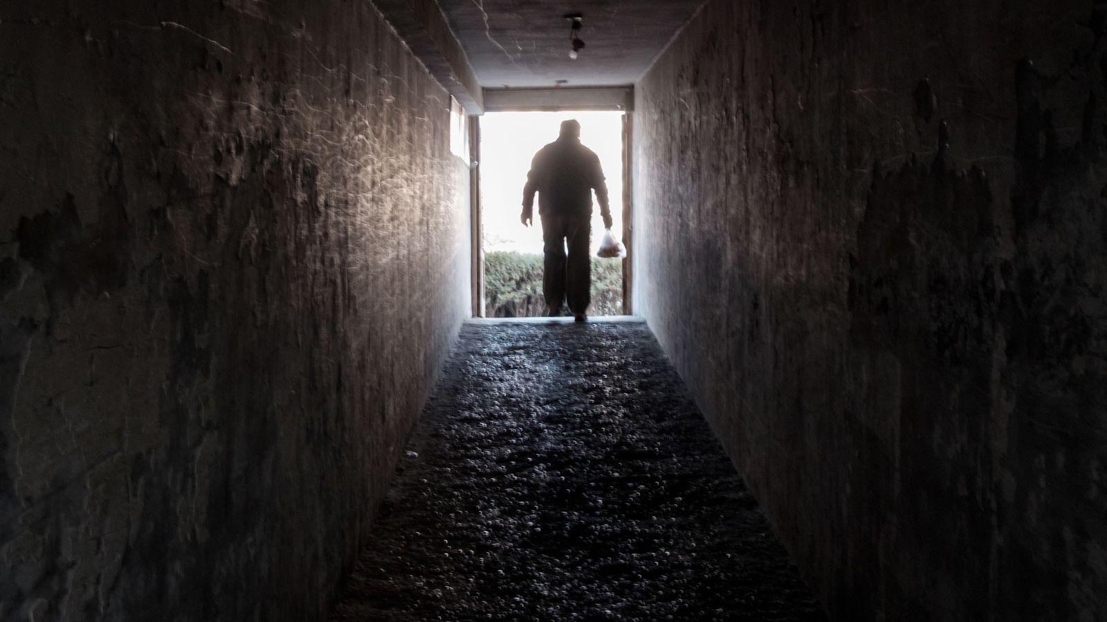Um homem sai de um abrigo nuclear.