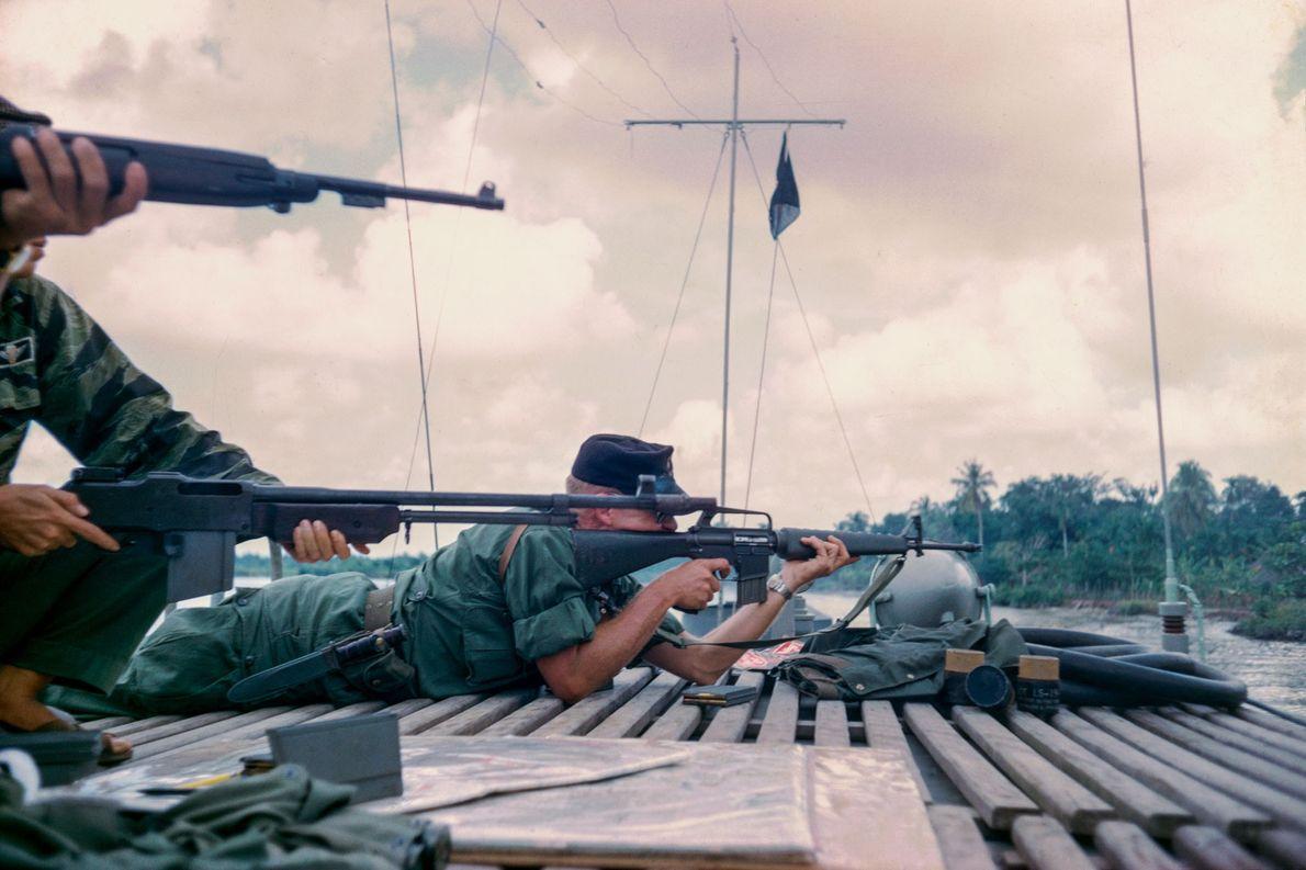 Um tenente da Marinha atira nos vietcongues do deck de seu barco de guerra no Mekong.