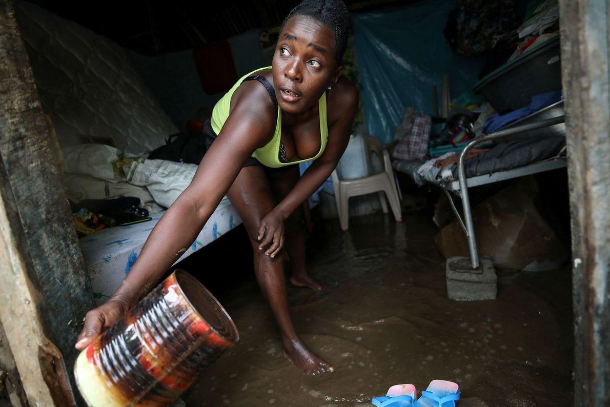 Uma mulher usa  lata para remover água em sua casa após o furacão Irma em ...