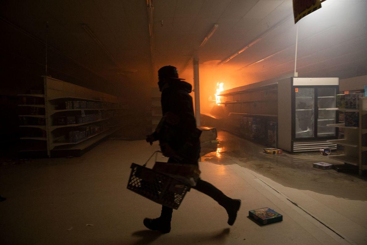 Manifestantes saqueiam uma loja de departamentos durante as manifestações. Cerca de 200 empresas em Minneapolis e ...