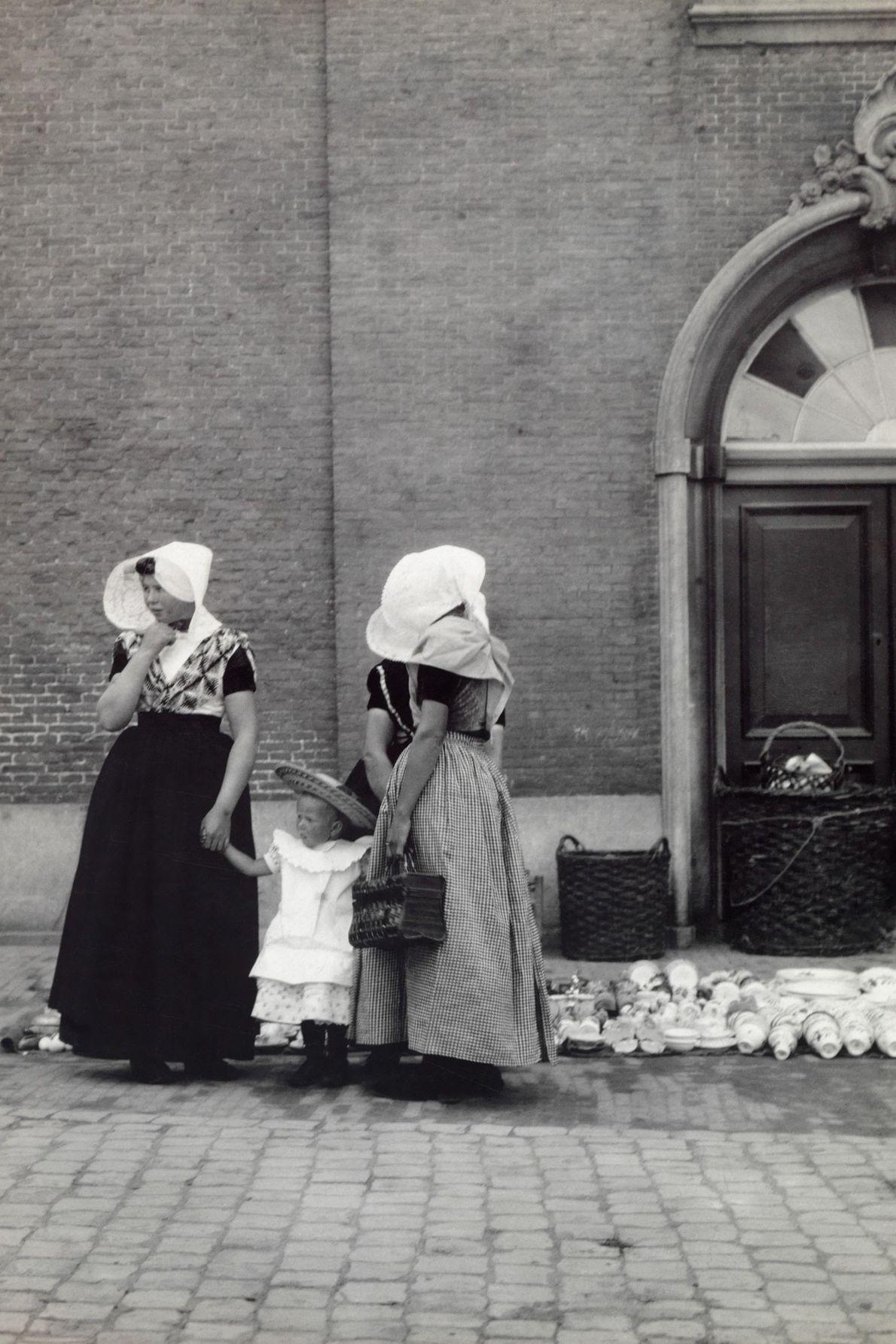 Uma mulher e sua empregada seguram as mãos de uma criança pequena enquanto compram louças em ...