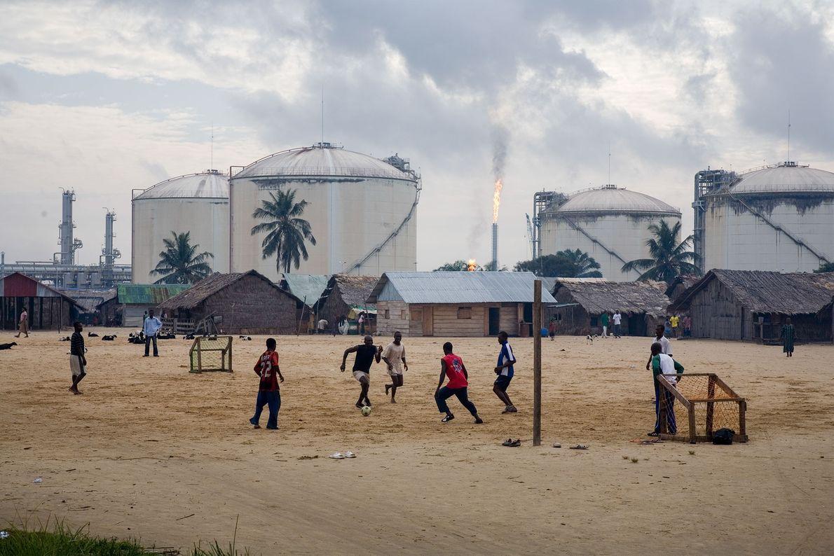 Homens jovens jogam futebol em frente a tanques de armazenamento de gás em Bonny Island, Nigéria.