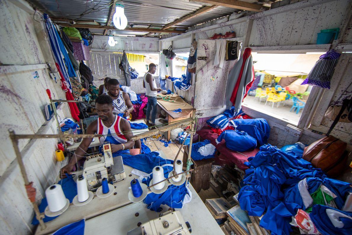 Homens tabons trabalham em oficina de alfaiataria em Acra, Gana. O ofício trazido pelos primeiros afro-brasileiros …