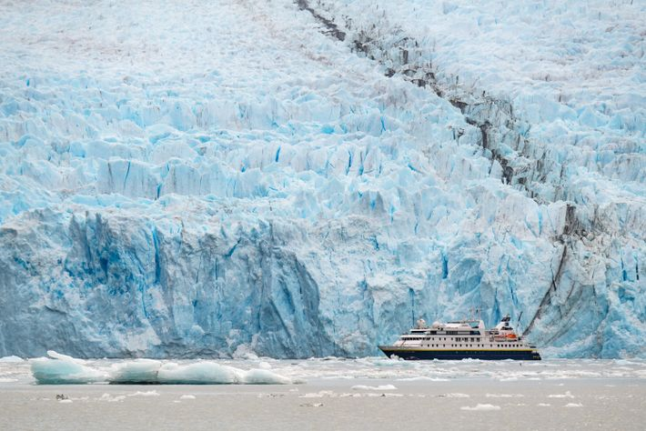 O National Geographic Orion parece um barco de brinquedo em frente à enorme Geleira Garibaldi, na ...