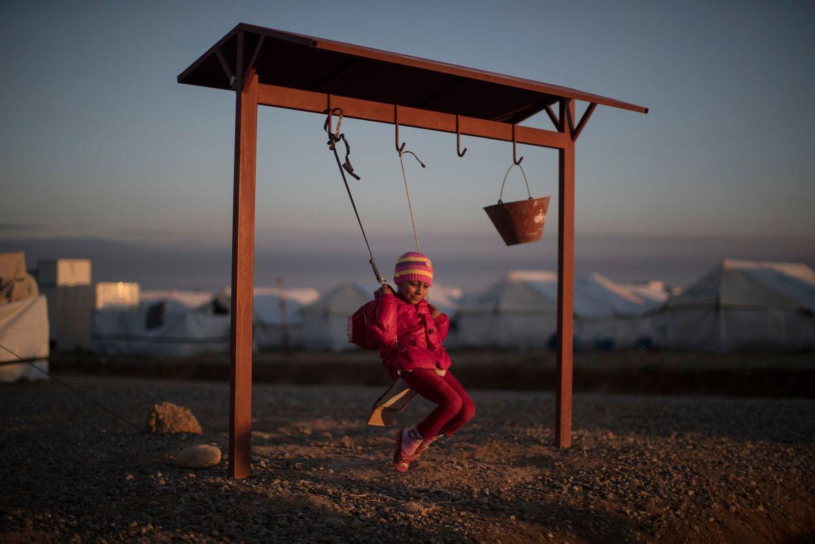 Garota iraquiana refugiada, deslocada depois da guerra entre forças iraquianas e militantes do Estado Islâmico, brinca ...