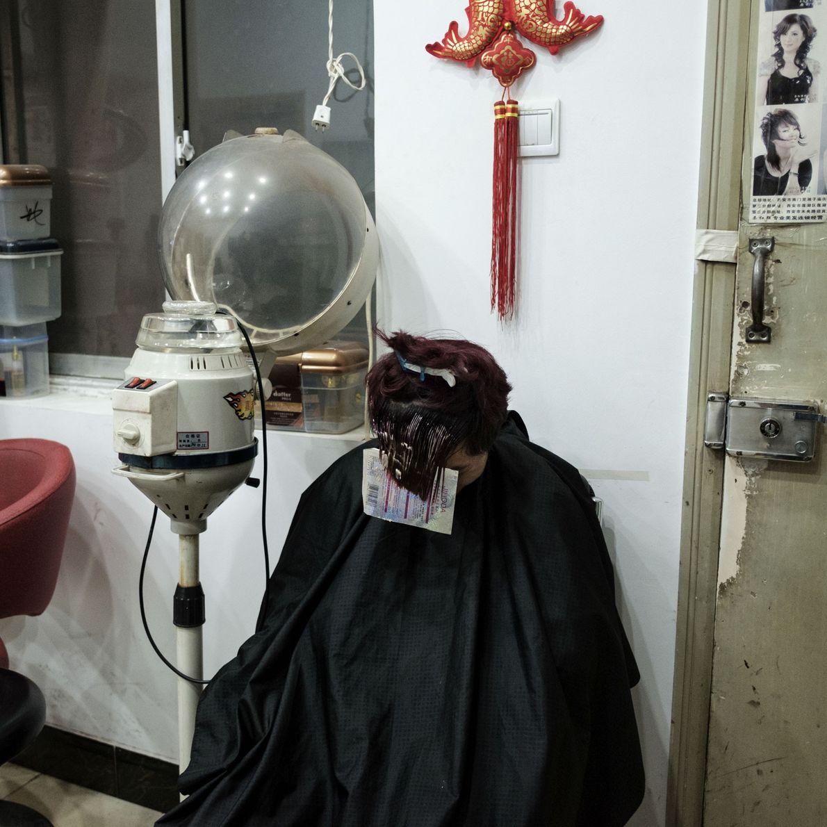 Um menino tinge o cabelo em uma barbearia subterrânea no distrito de Da Hong Men. Estimativas ...