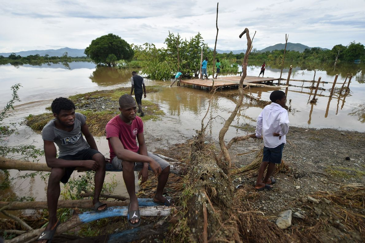 As pessoas sentam-se em árvore ao lado de rio inundado no Haiti após o furacão Irma ...