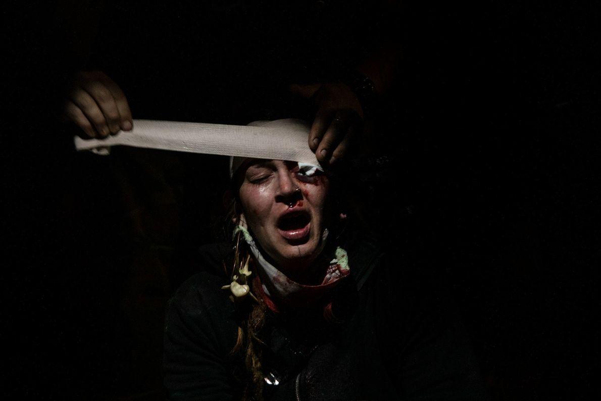 Uma manifestante sendo socorrida no estacionamento de uma loja de departamentos depois de ter sido atingida ...
