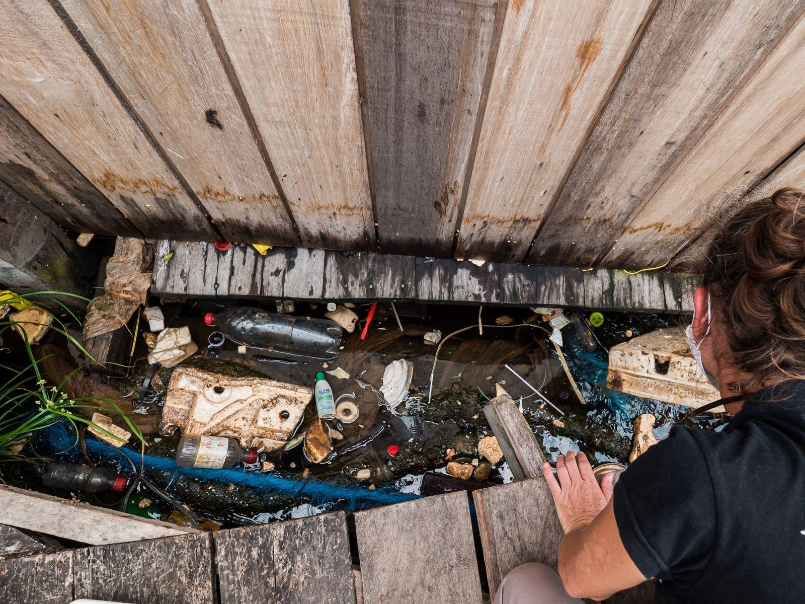 Resíduos se acumulam embaixo dos flutuantes ao longo do rio Negro, nas proximidades de Manaus. Mas ...