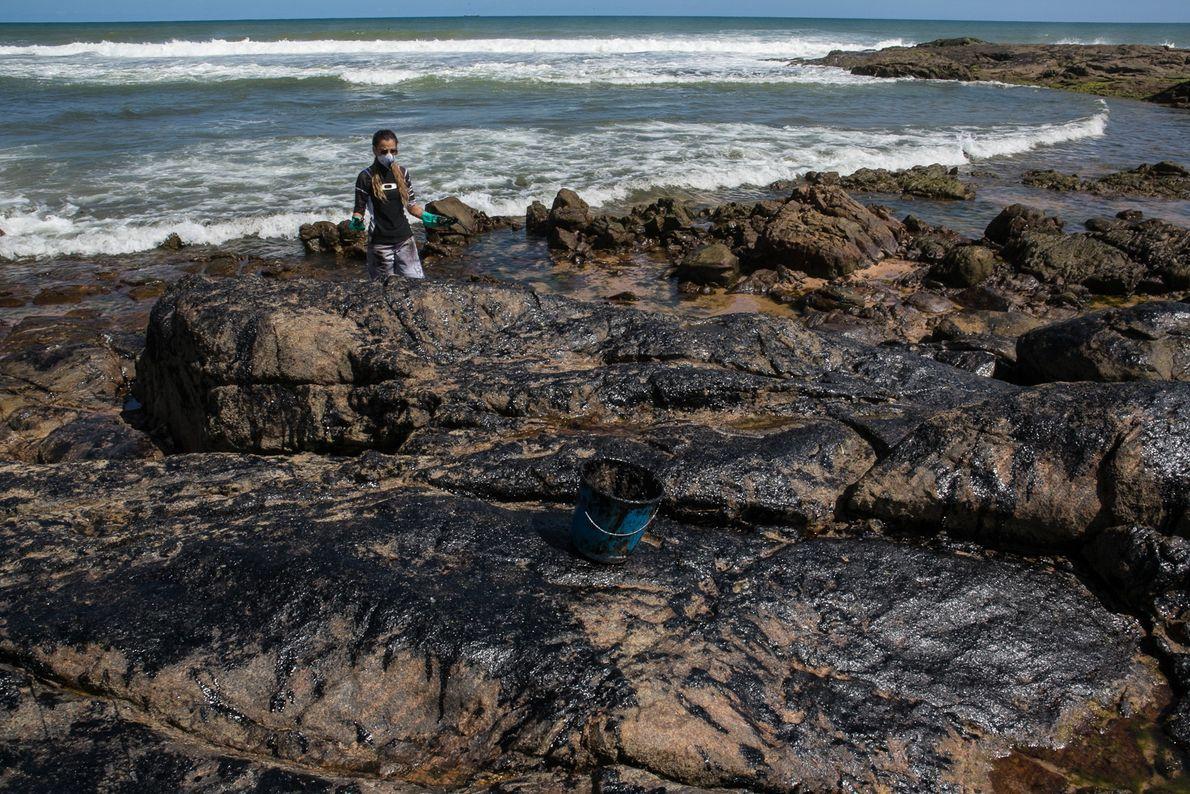 Luana, uma voluntária moradora da região, ajuda a limpar as pedras na famosa praia da Pedra ...