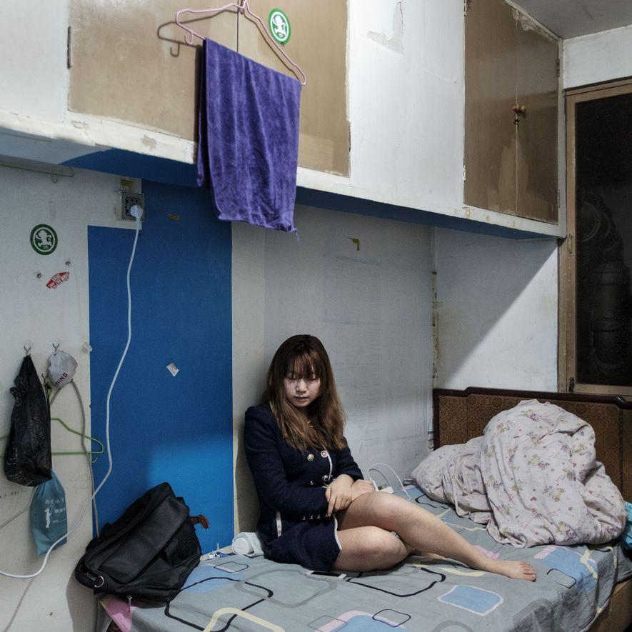 Xian, 23 anos, está sentada na cama em seu quarto, no abrigo atômico de Nong Ying, …