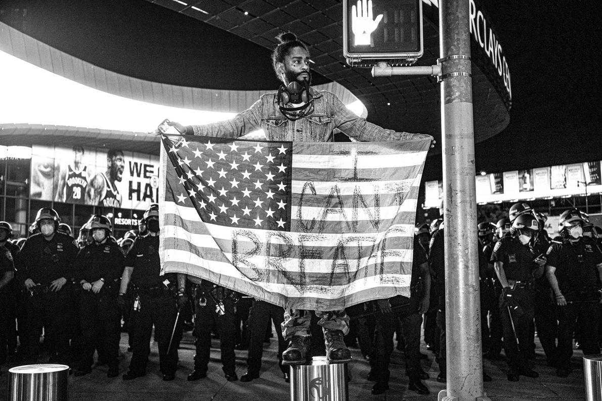 """Um homem que se intitula """"Royal G"""" se posiciona na frente de policiais segurando uma bandeira ..."""