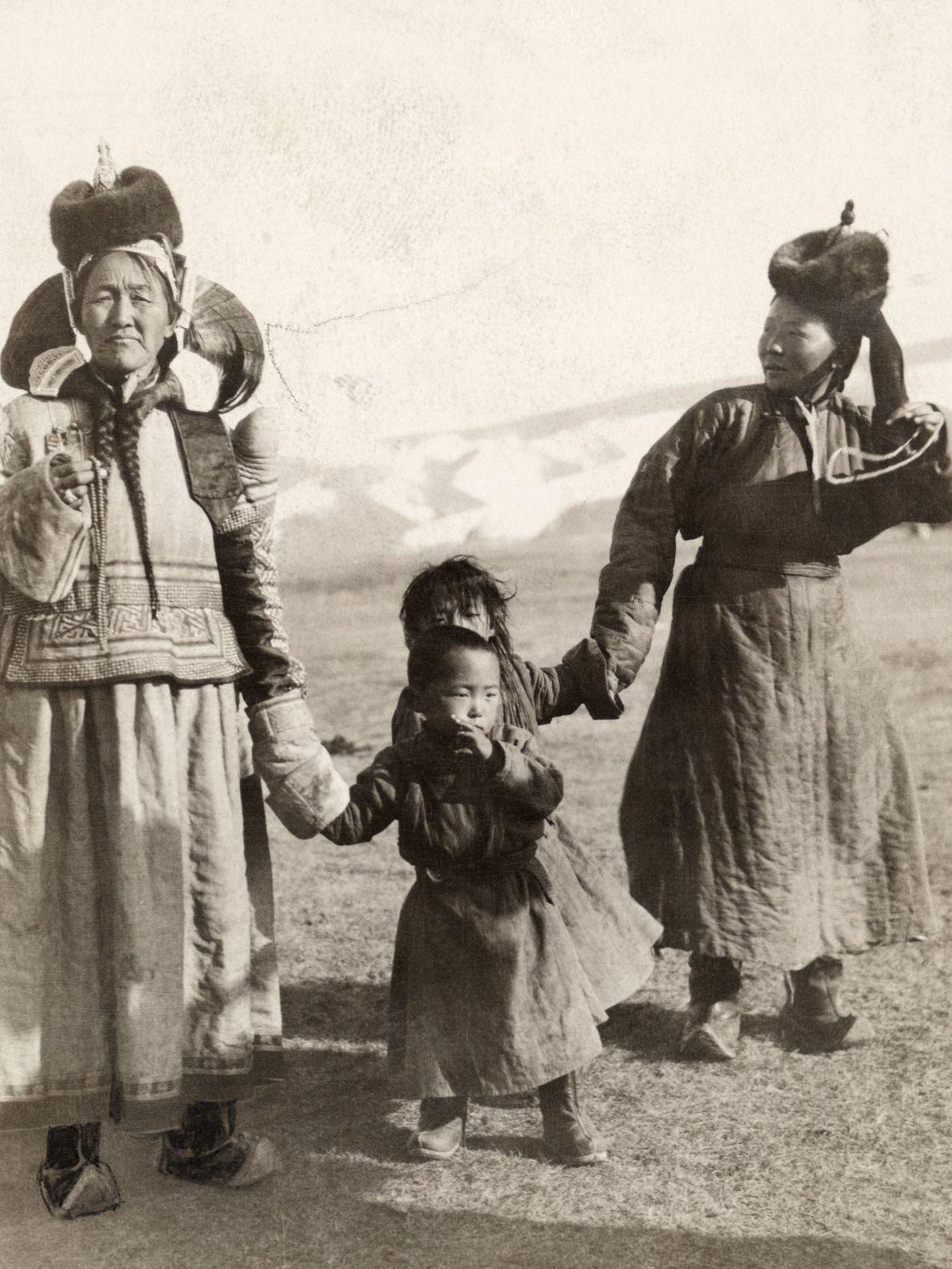 Mulheres andam de mãos dadas com seus filhos na Mongólia.