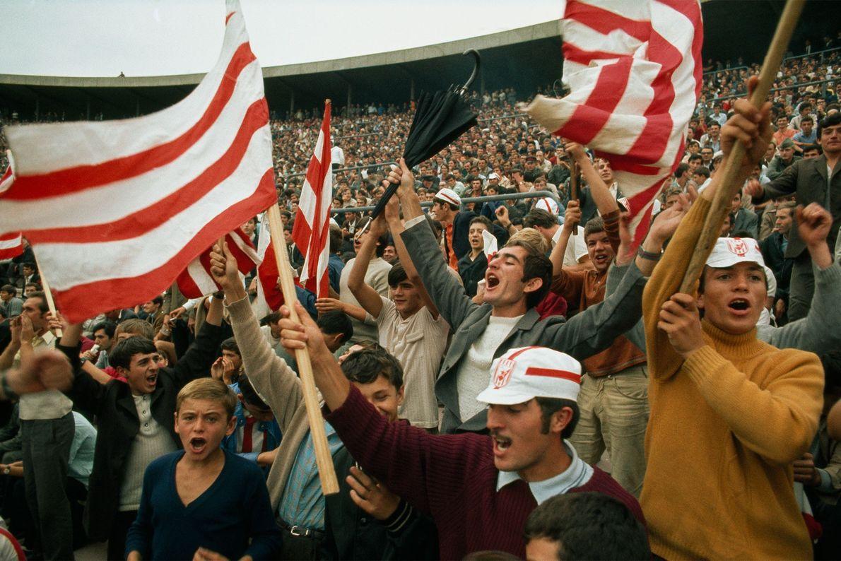 Durante um jogo de futebol de 1970 na Sérvia, Iugoslávia, fãs comemoram um gol da Iugoslávia ...