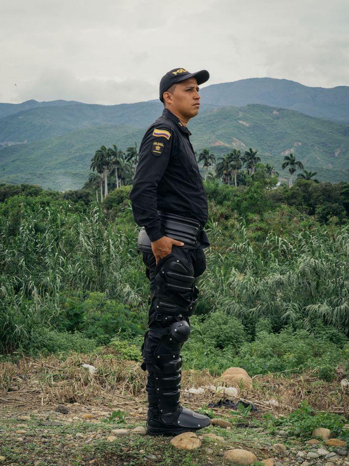 O policial Jeo Vanny Tamara observa de longe enquanto milhares de venezuelanos atravessam a ponte Simón ...