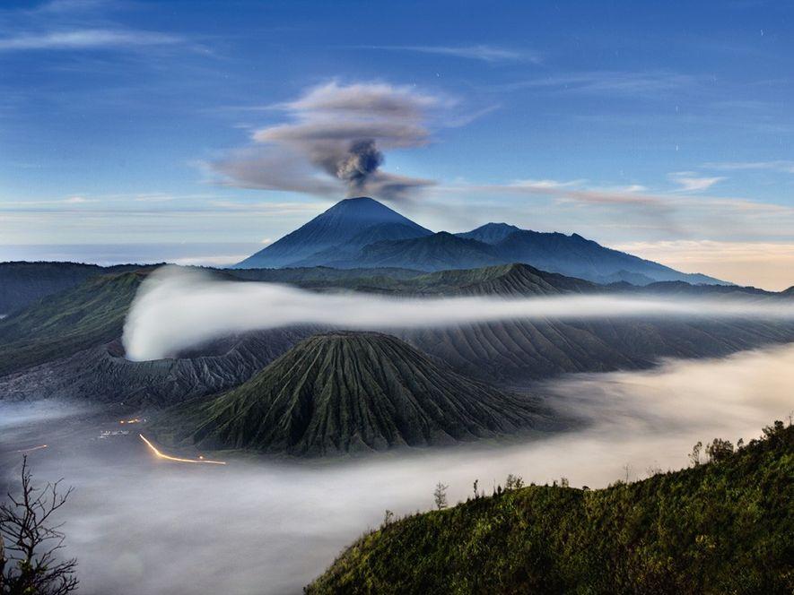 O monte Semeru, visto com uma nuvem de fuligem, é o mais alto vulcão na ilha ...