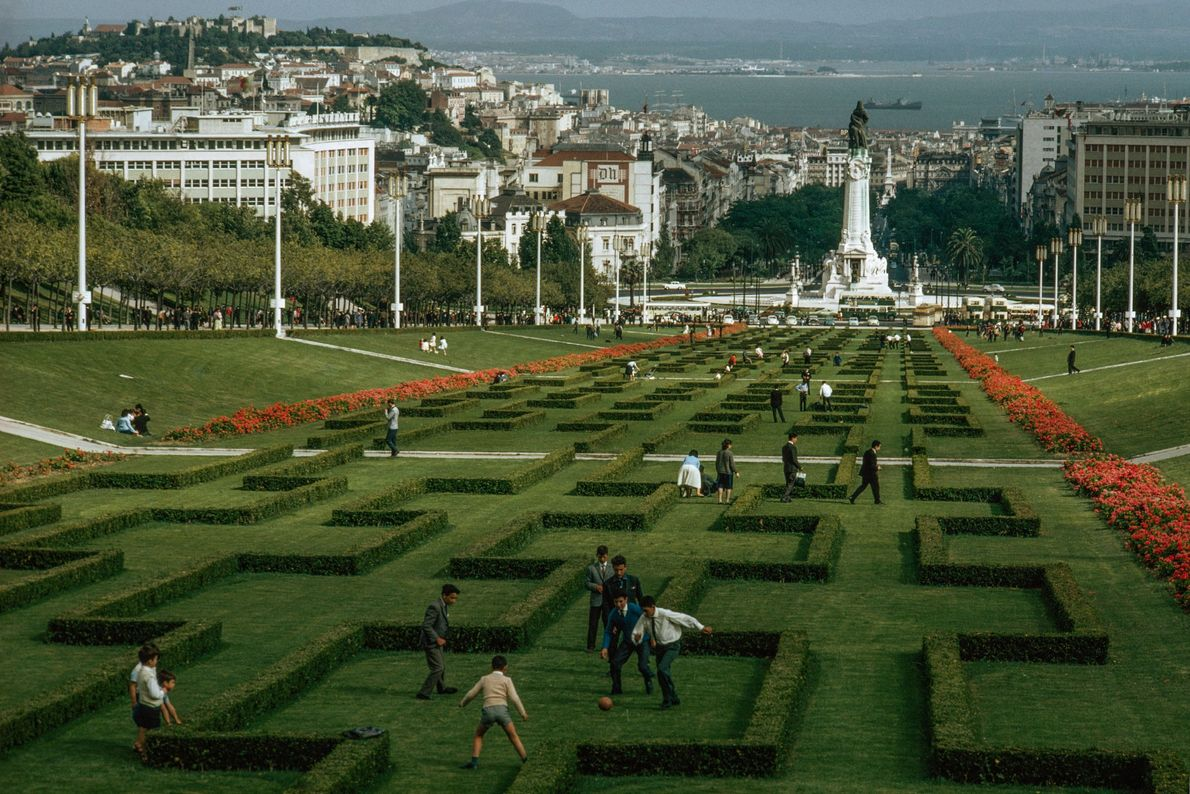 Pessoas caminham por um jardim em Lisboa, Portugal, enquanto um grupo de meninos jogam futebol.