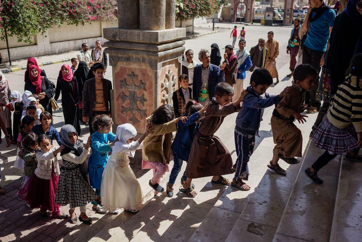 Pais e filhos entregam oferendas simbólicas de poucas moedas a um correio em Sanaa, protestando contra ...